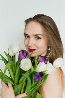 Piękna Kobieta Trzyma Duży Bukiet. Młoda Kobieta Z Bukietem Tulipanów Premium Zdjęcia