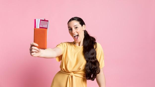 Piękna kobieta trzyma jej paszport i samolotowi bilety