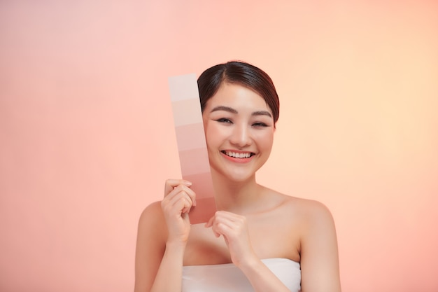 Piękna kobieta trzyma kartę kolorów pod ochroną przeciwsłoneczną na beżowym tle