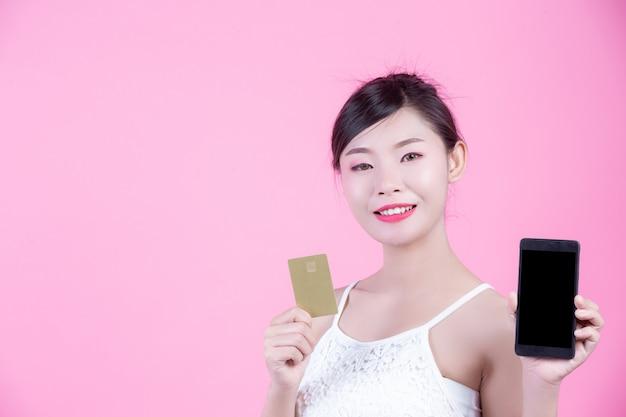 Piękna kobieta trzyma kartę na różowym tle i smartphone