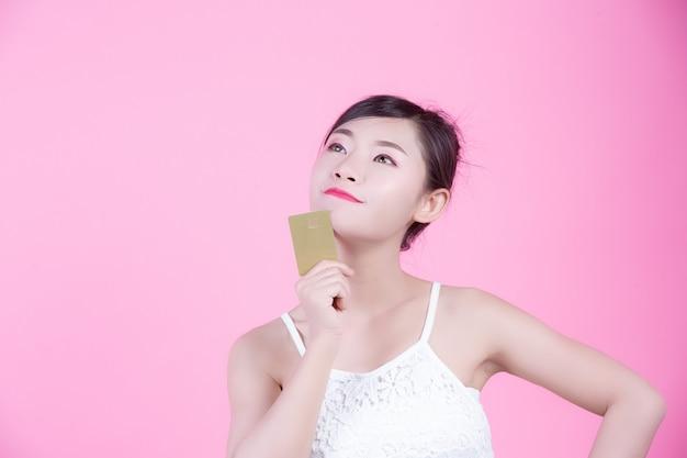Piękna kobieta trzyma kartę na różowym tle.