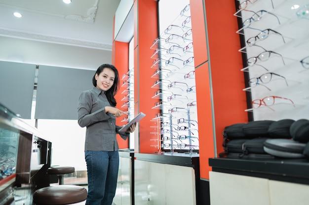 Piękna kobieta trzyma katalog produktów do okularów dostępnych po badaniu wzroku w klinice okulistycznej