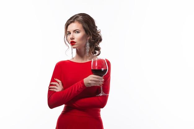 Piękna kobieta trzyma kieliszek wina na białym tle
