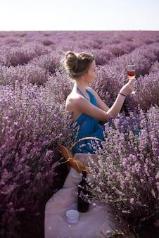 Piękna kobieta trzyma kieliszek wina różowego. dziewczyna zrelaksuje się na pikniku z serem camembert, francuską bagietką i winem