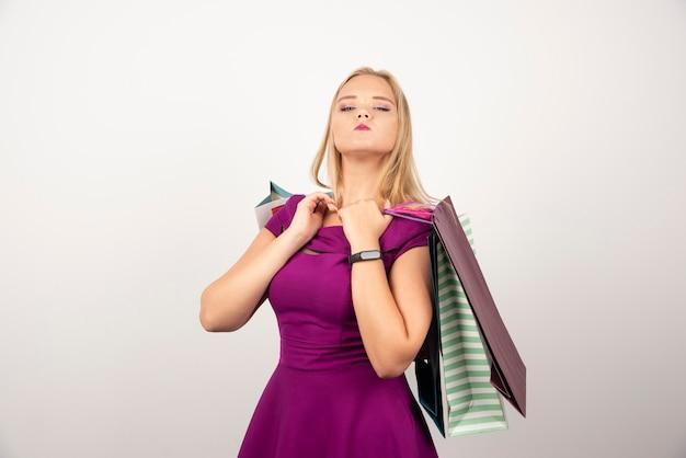 Piękna kobieta trzyma kilka toreb na zakupy na białym.