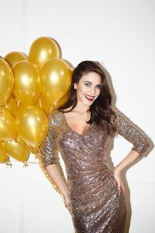Piękna kobieta trzyma kilka złotych balonów