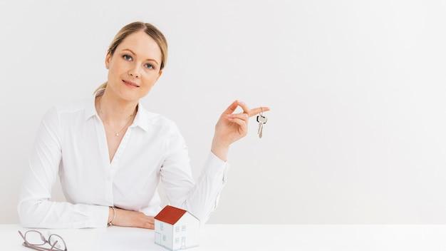 Piękna kobieta trzyma klucze patrząc na kamery