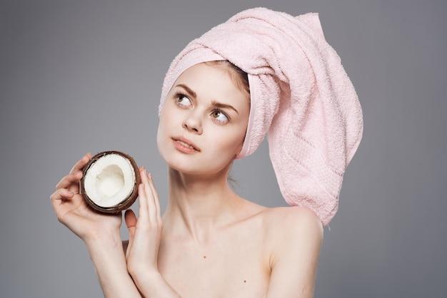 Piękna kobieta trzyma kokos z nagimi ramionami