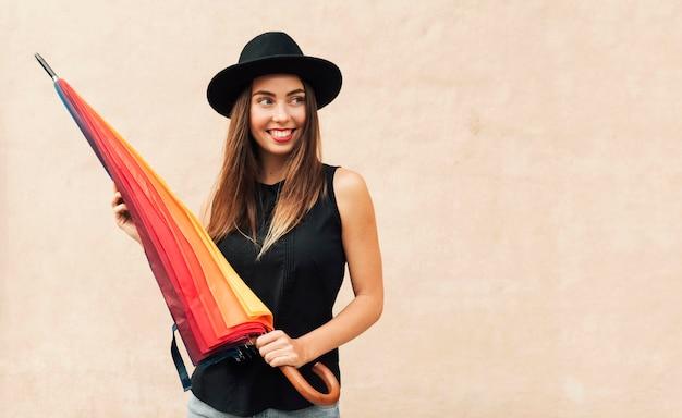 Piękna kobieta trzyma kolorowy parasol z miejsca na kopię