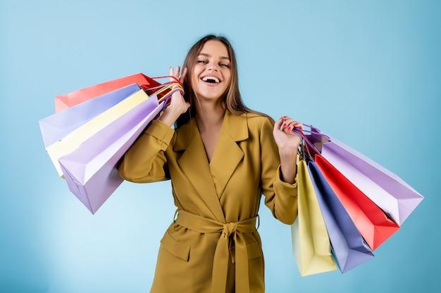 Piękna kobieta trzyma kolorowych torba na zakupy odizolowywający nad błękitem