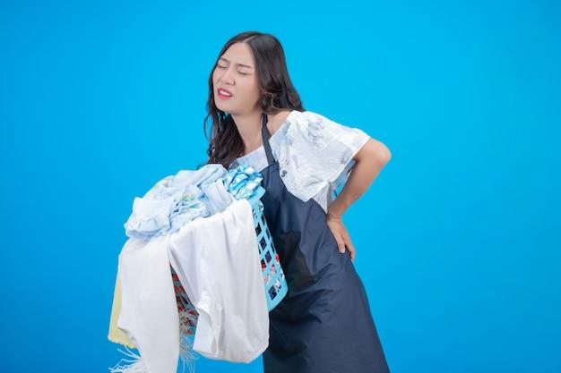 Piękna kobieta trzyma kosz ubrania na błękicie