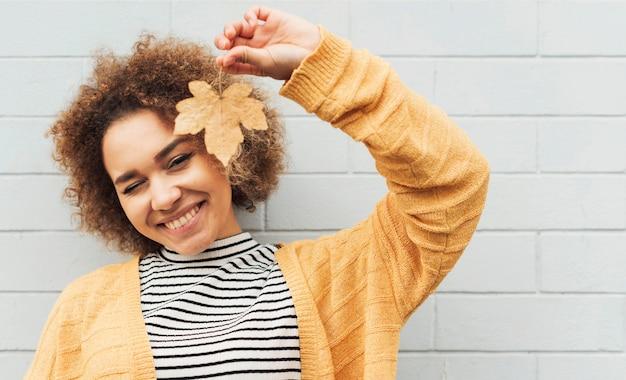 Piękna kobieta trzyma liść do góry nogami