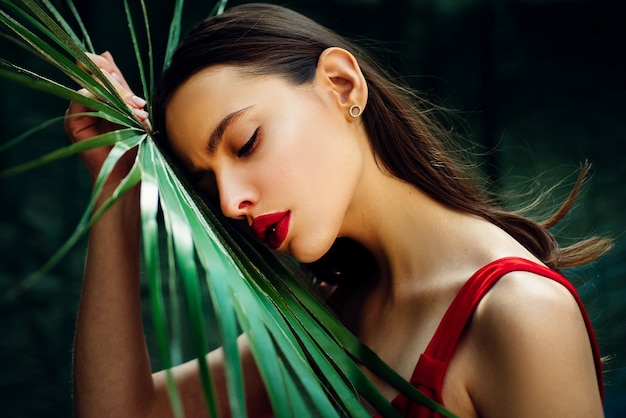 Piękna kobieta trzyma liść palmy.