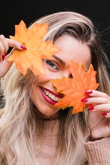 Piękna kobieta trzyma liście klonu przed jej twarzą
