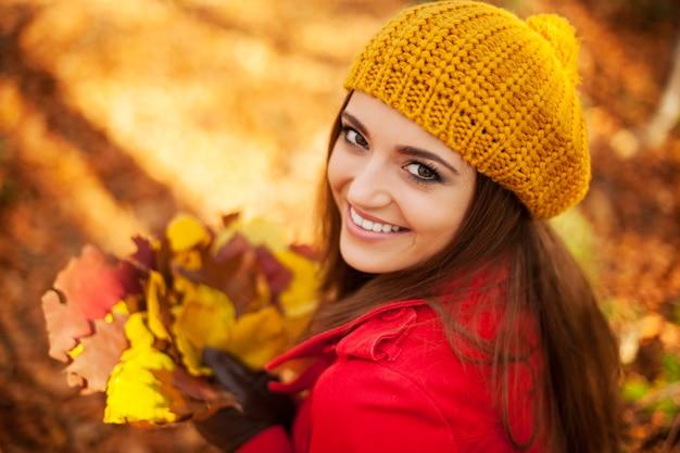 Piękna kobieta trzyma liście w słoneczny jesienny dzień