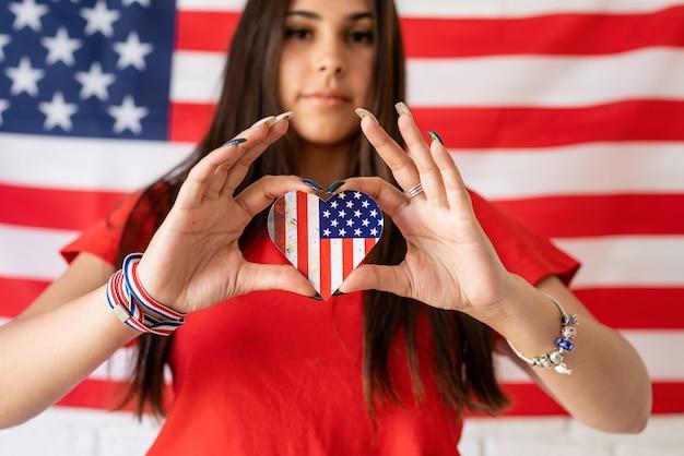 Piękna kobieta trzyma małą flagę narodową na tle flagi usa
