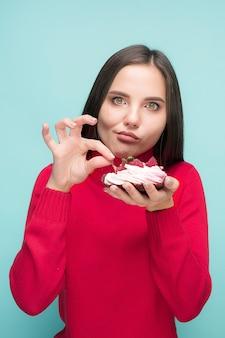Piękna kobieta trzyma małe ciasto