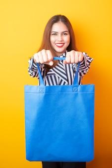 Piękna kobieta trzyma niebieską sukienną torbę