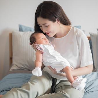 Piękna kobieta trzyma nowonarodzonego dziecka w ona ręki