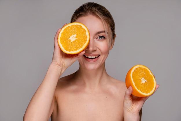 Piękna kobieta trzyma o połowę pomarańczy