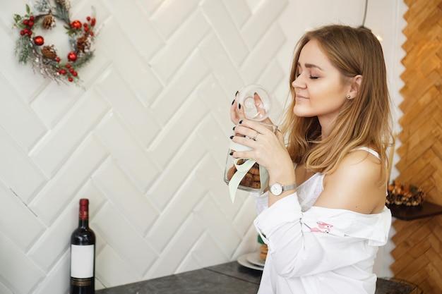 Piękna kobieta trzyma pachnące ciasteczka z zamkniętymi oczami. cieszący się jedzeniem plakat z miejscem na tekst. piękna dziewczyna ubrana w białą koszulę