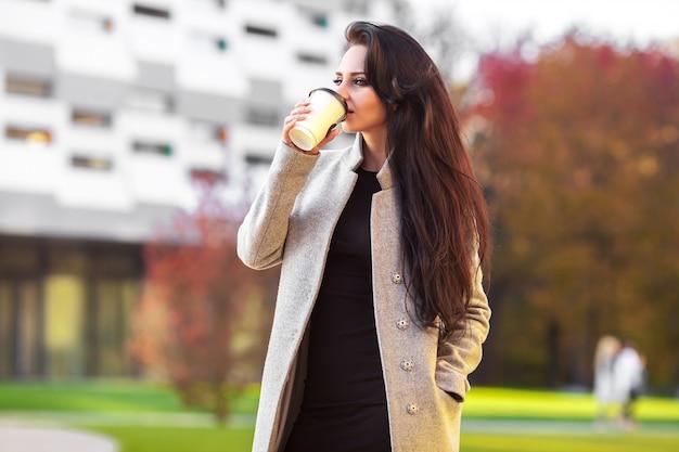 Piękna kobieta trzyma papierową filiżankę i cieszy się spacer w mieście
