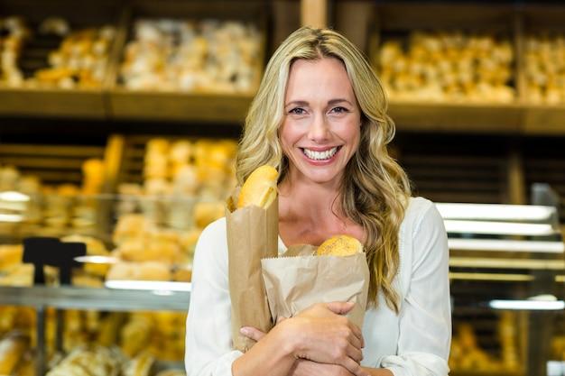 Piękna kobieta trzyma papierową torbę z chlebem