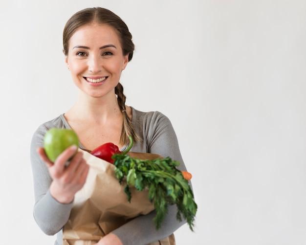Piękna kobieta trzyma papierową torbę z owoc i warzywo