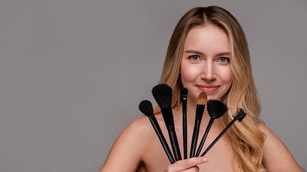 Piękna kobieta trzyma pędzle do makijażu