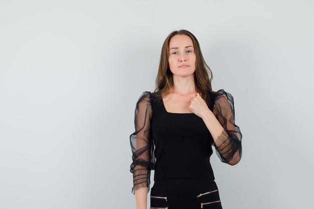 Piękna kobieta trzyma pięść na piersi w czarnej bluzce i wygląda imponująco. przedni widok. miejsce na tekst