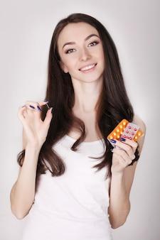Piękna kobieta trzyma pigułki antykoncepcyjne, doustne środki antykoncepcyjne