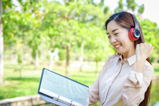 Piękna kobieta trzyma plik i nosi słuchawki jest szczęśliwa do pracy.