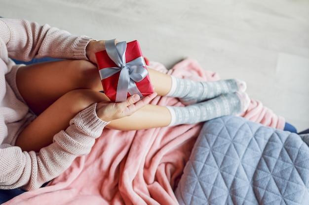 Piękna kobieta trzyma prezent na kanapie