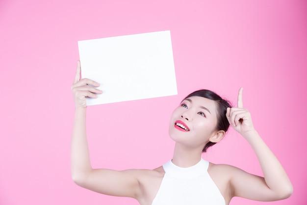 Piękna kobieta trzyma prześcieradło białej deski na różowym tle.
