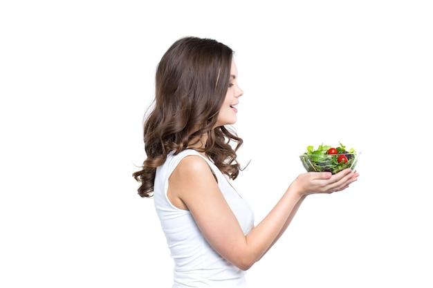 Piękna kobieta trzyma przezroczystą miskę ze zdrowym posiłkiem sałatkowym, patrząc na miskę, na białym, z miejsca na kopię. zdrowy tryb życia.