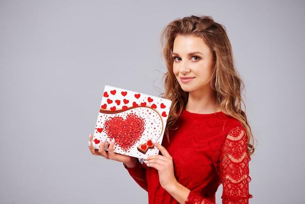 Piękna kobieta trzyma pudełko czekoladek w kształcie serca