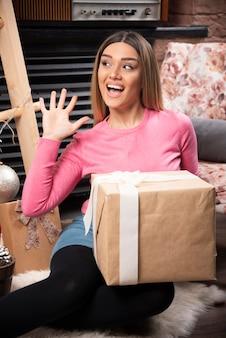 Piękna kobieta trzyma pudełko z szczęśliwym wyrazem twarzy w domu