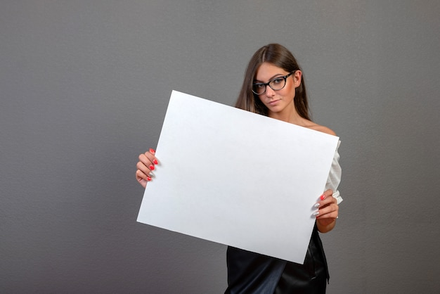 Piękna kobieta trzyma pustego billboard