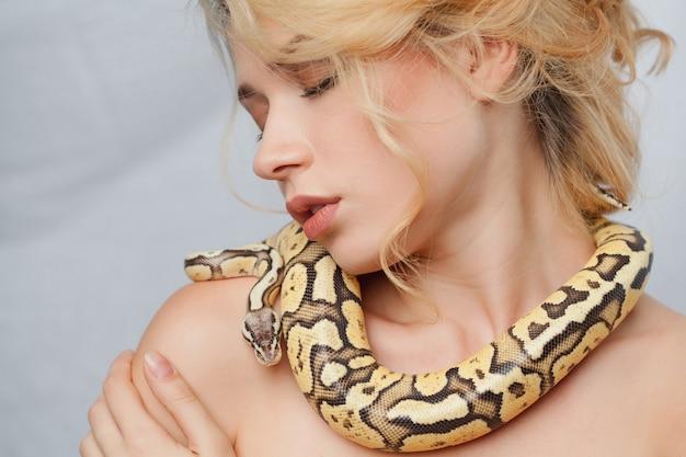 Piękna kobieta trzyma pytona, który owija się wokół jej ciała