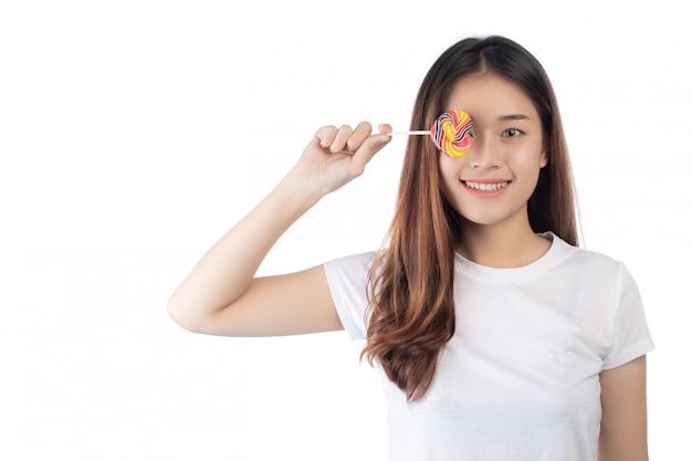 Piękna kobieta trzyma ręka cukierek z szczęśliwym uśmiechem, odizolowywającym na białym tle.