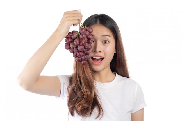 Piękna kobieta trzyma ręka winogrona z szczęśliwym uśmiechem, odizolowywającym na białym tle.