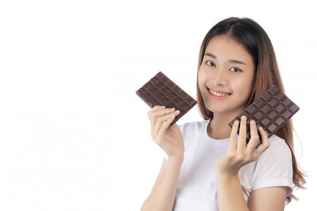 Piękna kobieta trzyma rękę czekoladę z szczęśliwym uśmiechem