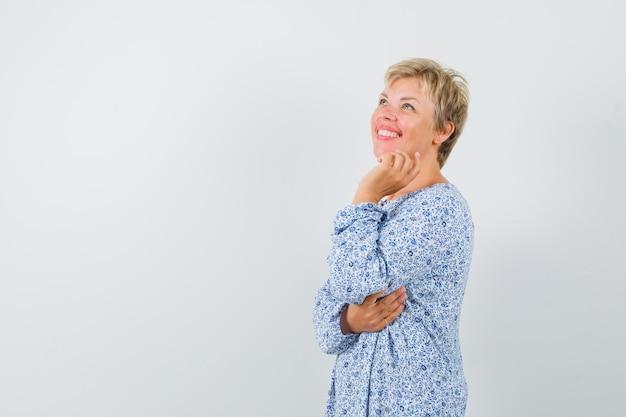 Piękna kobieta trzyma rękę na jej szczęce we wzorzystej bluzce i szuka życzenia, widok z przodu. miejsce na tekst