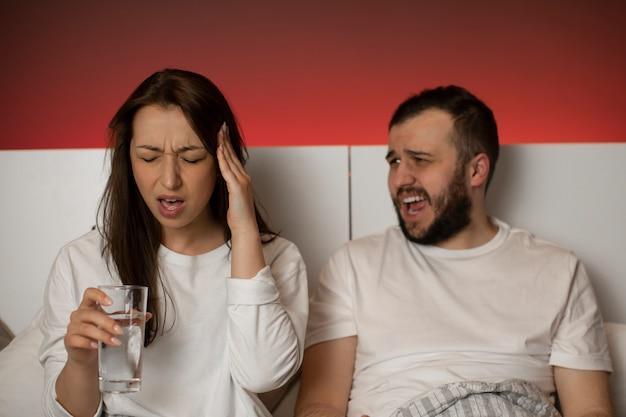 Piękna kobieta trzyma rękę w świątyni cierpi na migrenę, mężczyzna krzyczy na żonę