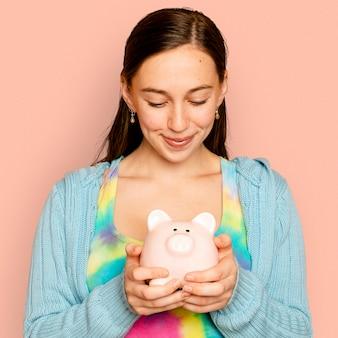 Piękna kobieta trzyma skarbonkę na kampanię oszczędności finansowych financial