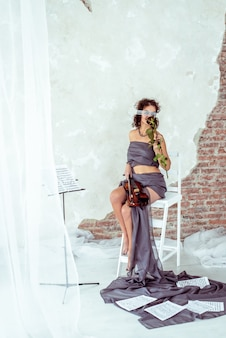 Piękna Kobieta Trzyma Skrzypce I Wącha Czerwieni Róży Premium Zdjęcia
