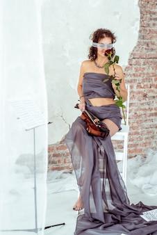 Piękna kobieta trzyma skrzypce i wącha czerwieni róży