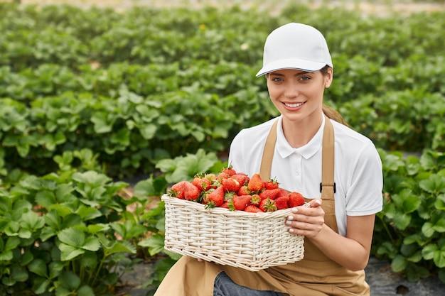 Piękna kobieta trzyma smaczną czerwoną truskawkę w koszyku