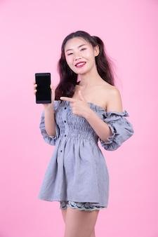 Piękna kobieta trzyma smartphone na różowym tle.