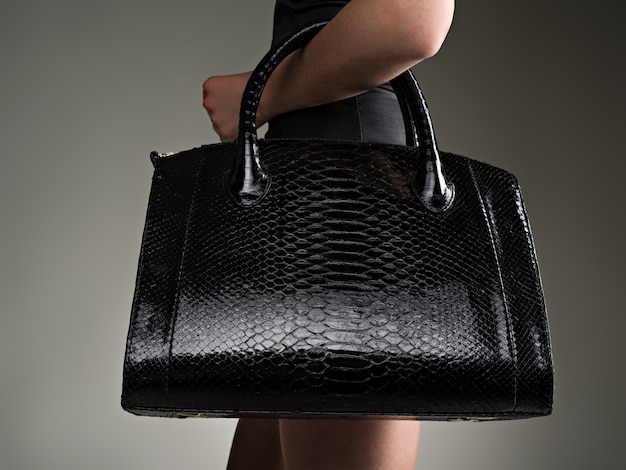 Piękna kobieta trzyma stylową czarną torbę. modna dziewczyna. stylowa koncepcja glamour. sztuka. kobieta po zakupach. nie do poznania kobieta.